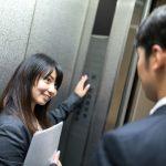 エレベーターのボタンを押す女性