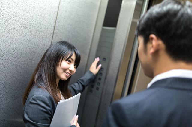 エレベーターのボタンを押す会社員女性