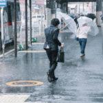 台風の中、傘をさして歩く男性