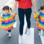 双子の子供が親と手を繋いでいる写真